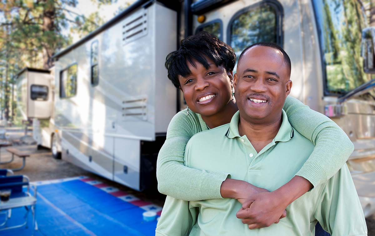 Happy couple in front of their recreation vehicle a campground after and RV inspection