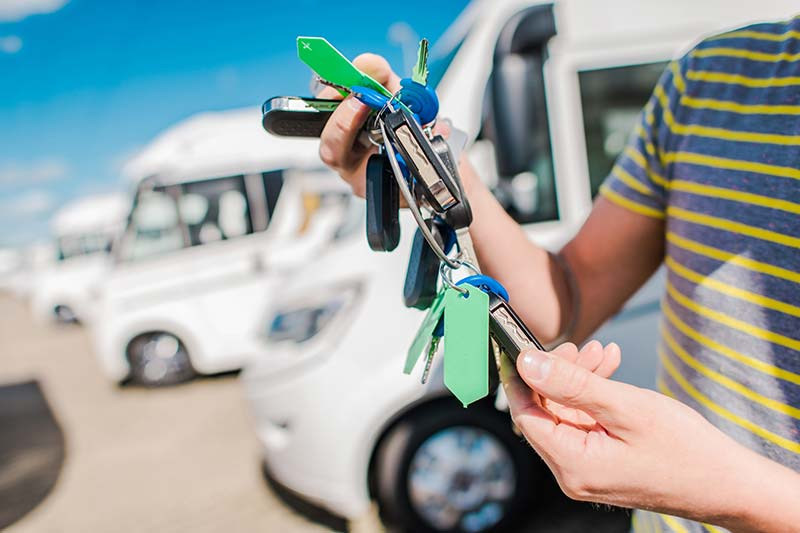 Person holding keys to a recreation vehicle they are selling after an rv inspection is preformed